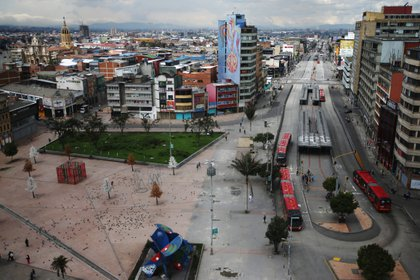 People and Transmilenio system buses are seen in the commercial area of San Victorino during the mandatory total isolation decreed by the mayor's office, amidst an outbreak of the coronavirus disease (COVID-19), in Bogota, Colombia January 8, 2021. REUTERS/Luisa Gonzalez