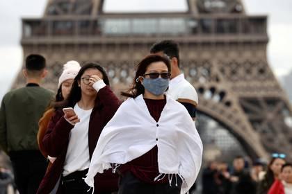 Turistas con mascarillas en París (Reuters)