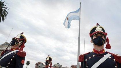 La bandera argentina flamea detrás de un grupo de Ganaderos que la escoltan