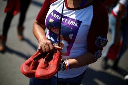 FOTO DE ARCHIVO-Una mujer sostiene un par de zapatos rojos, dispuestos por la artista visual mexicana Elina Chauvet para protestar contra la violencia de género y el feminicidio. (Foto: REUTERS/Gustavo Graf)