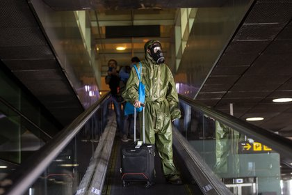 Un pasajero con un traje de protección llega desde Londres al aeropuerto de Barcelona, España, el viernes 15 de mayo de 2020 (Foto AP/Emilio Morenatti)
