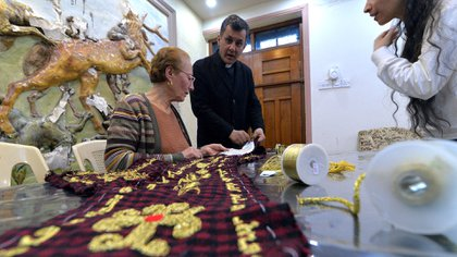 El sacerdote Ammar Yaqo observa el trabajo de la bordadora en Qaraqosh. (Zaid AL-OBEIDI / AFP)