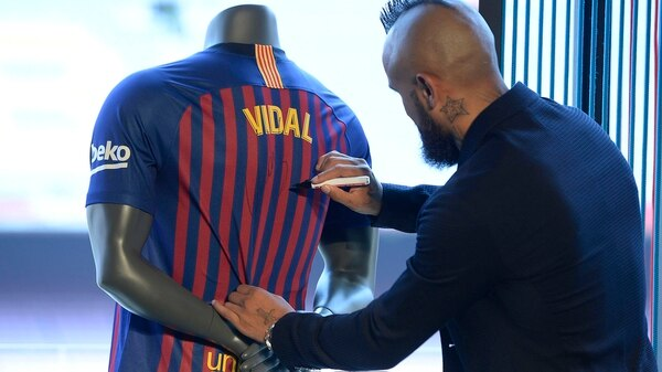 Barcelona's new player Chilean midfielder Arturo Vidal sings his new jersey during his official presentation at the Camp Nou stadium in Barcelona on August 6, 2018. / AFP PHOTO / Josep LAGO