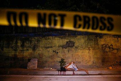 El cuerpo de otra víctima, muerta a tiros por pistoleros desconocidos, sangra detrás de una línea policial en Manila (Reuters)