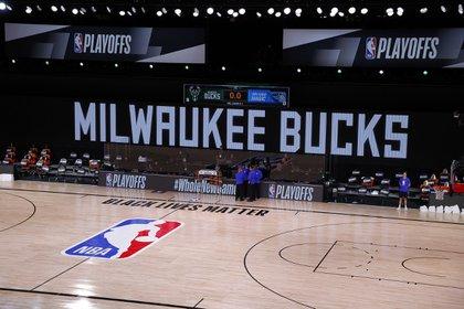 Los árbitros se reúnen en una cancha vacía para el juego entre los Milwaukee Bucks y Orlando Magic que finalmente no se disputó debido al boicot de los jugadores