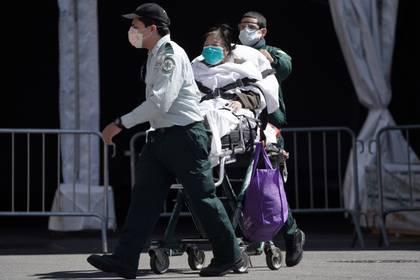 Una persona es llevada en silla de ruedas a una ambulancia fuera de un hospital durante el brote de coronavirus en Nueva York, EE.UU., 2 de abril de 2020. (REUTERS/Carlo Allegri)