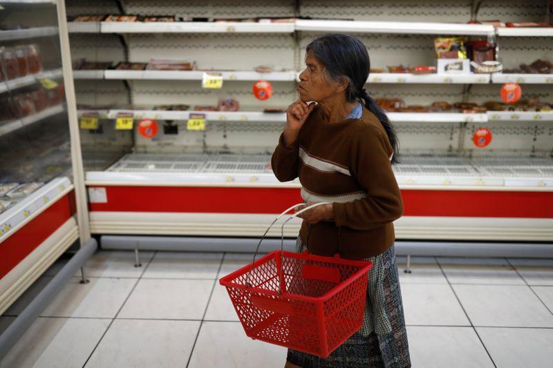 Una mujer mira estantes vacíos en un supermercado después de que el gobierno de Guatemala anunciara medidas para prevenir la propagación del coronavirus. 17 de marzo de 2020. REUTERS / Luis Echeverría