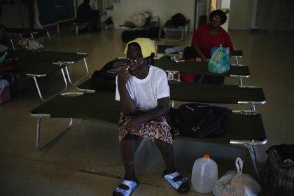 Dos mujeres sentadas en catres dentro de una iglesia empleada como refugio para los vecinos, que esperarán allí a que pase el huracán Dorian, en Freeport, Gran Bahama (AP Foto/ Ramón Espinosa)