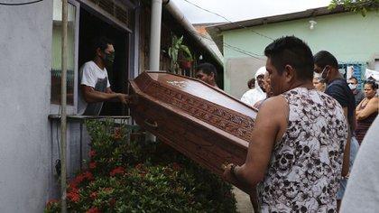 Familiares y amigos extraen por la ventana el ataúd con un fallecido por coronavirus en Manaos (AP/Edmar Barros)