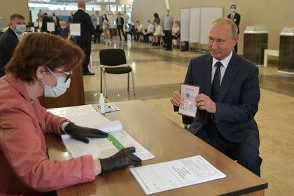 Vladimir Putin muestra su pasaporte durante su voto en el referéndum por la reforma constitucional el 1 de julio de 2020. (Sputnik/Alexei Druzhinin/Kremlin via REUTERS)