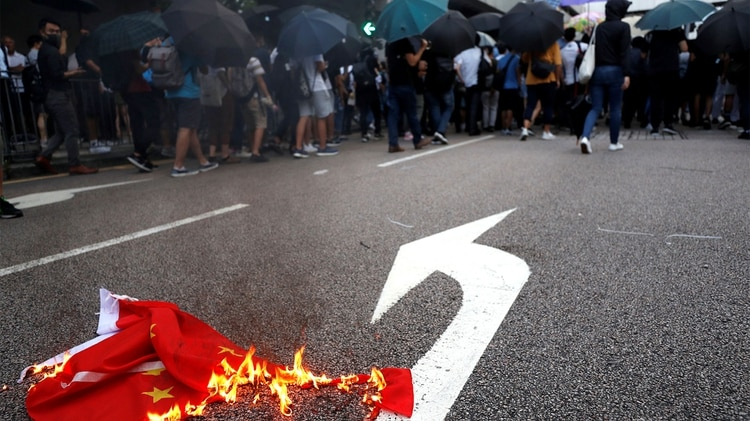 Una bandera china se quema mientras los manifestantes bloquean una calle en el centro de Hong Kong (REUTERS/Jorge Silva)
