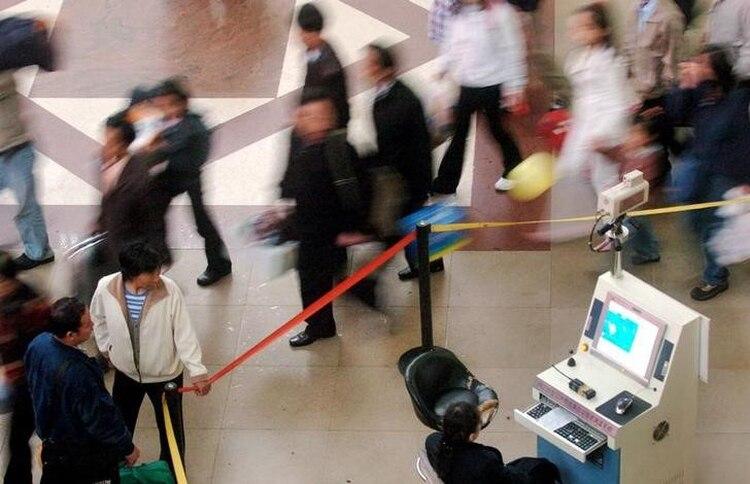 Un trabajador sanitario chino usa un monitor de temperatura por imagen para vigilar si alguno de los viajeros de una estación de tren de Pekín tienen fiebre, el 26 de abril de 2004, en medio de medidas de seguridad para contener un brote de un virus que provocó el Síndrome Respiratorio Agudo y Grave (SARS). REUTERS/China Photos ASW