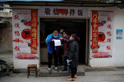 Members of a neighbourhood committee register a local and ask about his travel history in Jiujiang, Jiangxi province, China, as the country is hit by an outbreak of novel coronavirus.  February 2, 2020.  REUTERS/Thomas Peter