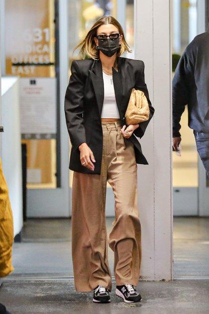 Hailey Bieber visitó a su médico en Beverly Hills y marcó tendencia con su look: un pantalón de gabardina clarito, una remera blanca y un saco negro. Combinó su cartera con su pantalón y completó su outfit con lentes de sol y zapatillas