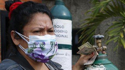 Videlba Reyes esperando para recargar oxígeno (Pedro Rances Mattey / AFP)