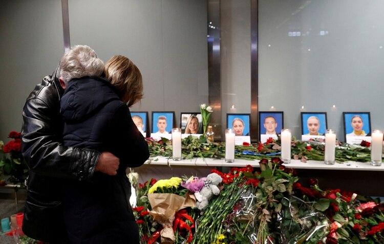 Los familiares de los miembros de la tripulación de vuelo del avión Boeing 737-800 de Ukraine International Airlines que se estrelló en Irán, lloran en un monumento en el aeropuerto internacional de Boryspil a las afueras de Kiev, Ucrania, el 8 de enero de 2020. (REUTERS / Valentyn Ogirenko)