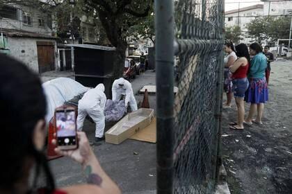 Trabajadores de una funeraria usando trajes protectores sacan el cuerpo de un hombre que murió en una calle en la comunidad de Arara tras sufrir problemas respiratorios en plena pandemia de coronavirus, en Rio de Janeiro (Reuters)