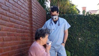 El Dr. Villar chequeando a una paciente con un nebulizador portátil y a pila con tecnología MESH