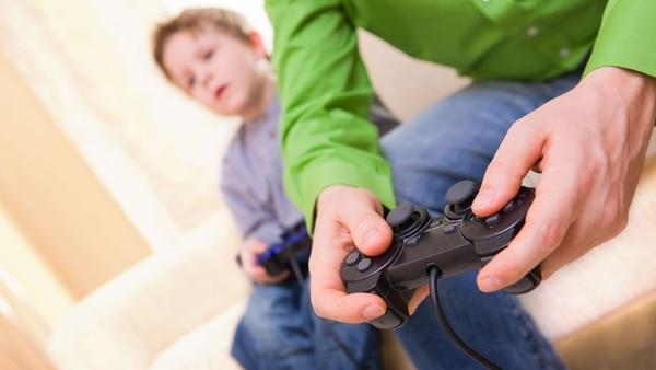 Recreación de un padre junto a su hijo con la consola (iStock)