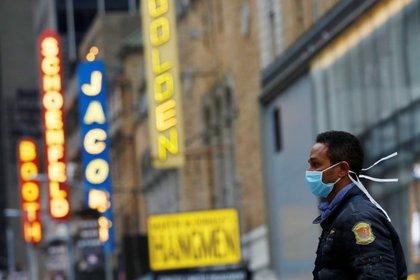 Un hombre camina por el distrito de teatros de Broadway de Manhattan en Nueva York, el 12 de marzo de 2020. REUTERS/Andrew Kelly