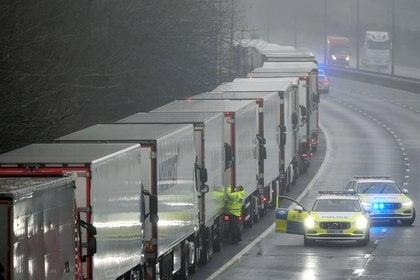 Agentes de policía hablan con un conductor en uno de los camiones estacionados en la autopista M20 hacia Eurotunnel y el puerto de Dover, mientras los países de la UE imponen una prohibición de viajar desde el Reino Unido tras el brote de la enfermedad por coronavirus (COVID-19), en Folkestone, Gran Bretaña (Reuters)