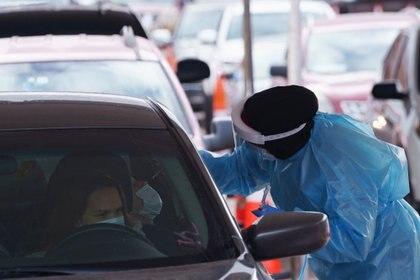 Una enfermera toma una muestra de hisopo en un lugar de prueba de la enfermedad coronavirus (COVID-19) en la Universidad de Texas (Reuters)