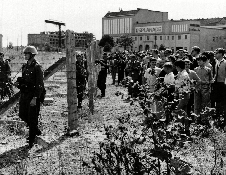 Vecinos de Berlín occidental se juntan frente a los primeros postes y alambres custodiados por guardias orientales el 13 de agosto de 1961.