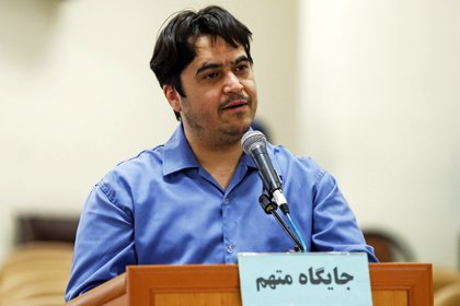 In this June 2, 2020 photo, journalist Ruhollah Zam speaks during his trial at the Revolutionary Court in Tehran, Iran.  Iran Judiciary spokesman Gholamhossein Esmaili announced on Tuesday June 30, 2020 that Zam, a journalist whose work helped inspire the 2017 economic protests and who returned from exile to Tehran, was sentenced to death.  The Persian writing on the podium says: