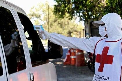 Un miembro de la Cruz Roja toma la temperatura en un cruce en Puerto Vallarta, Jalisco Foto: ULISES RUIZ / AFP