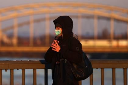 FOTO DE ARCHIVO: Una mujer con una máscara protectora cruza un puente en Fráncfort, Alemania, el 24 de marzo de 2020, mientras continúa la propagación de la enfermedad coronavirus (COVID-19).   REUTERS/Kai Pfaffenbach