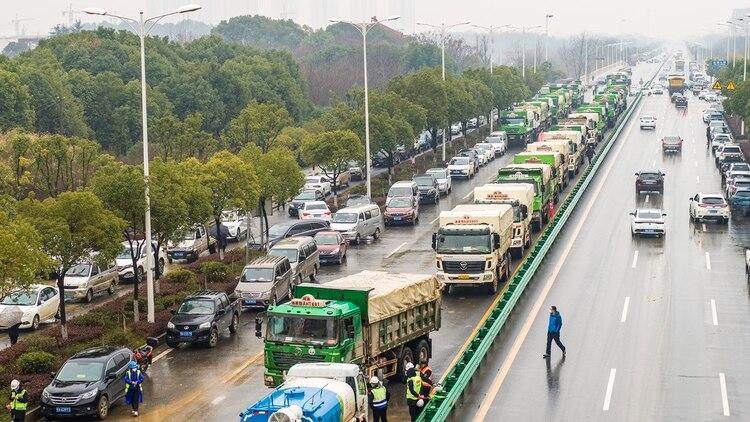 Los camiones esperan su turno para cargar la tierra que será extraída del terreno en que se construirá el centro de salud. (Photo by STR / AFP) / China OUT