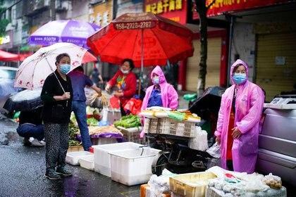 Varias personas con mascarillas en un mercado callejero en Wuhan, China (REUTERS/Aly Song)