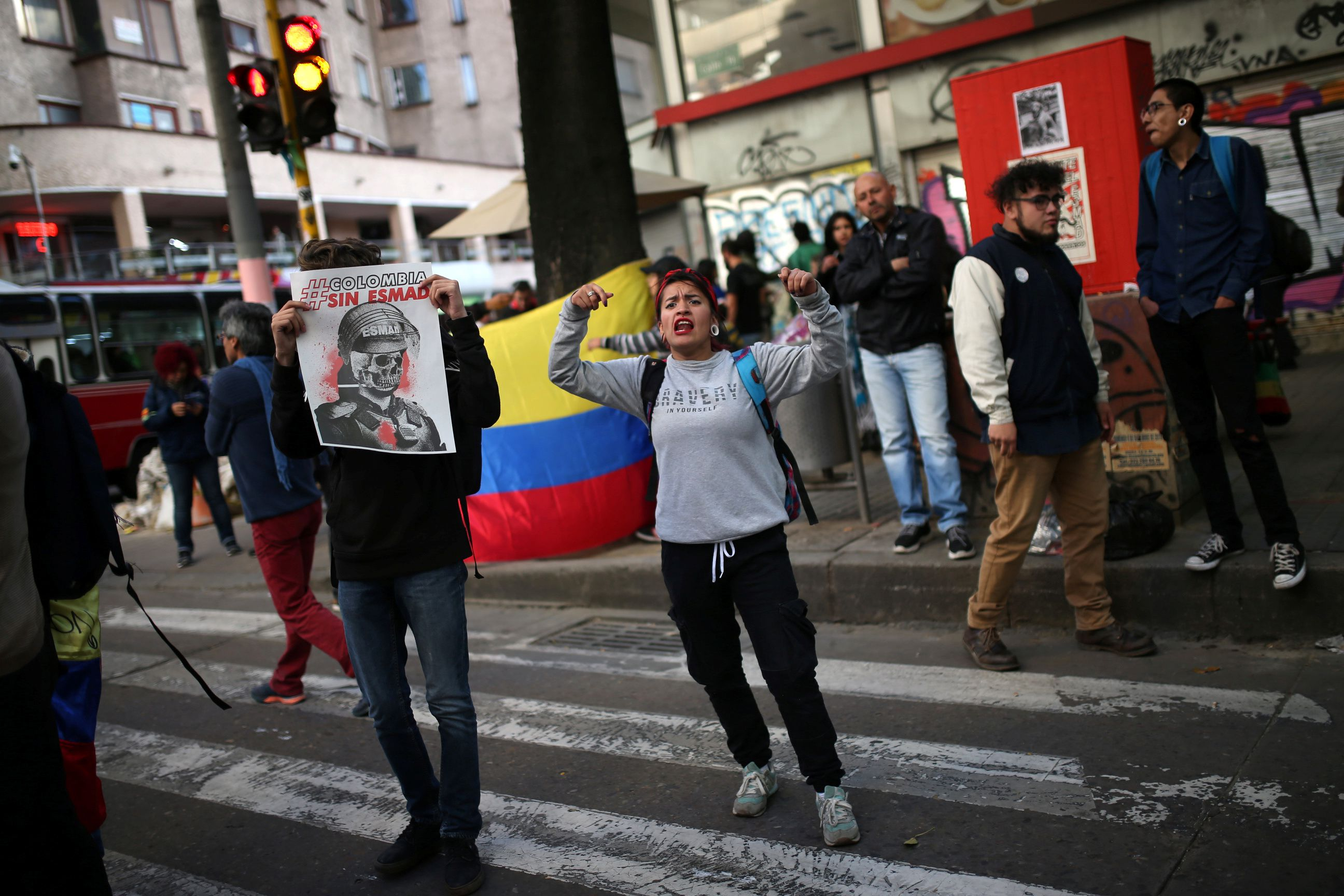 """A person holds a sign that reads """"Colombia without ESMAD"""" during a demonstration in honour of Dilan Cruz, a teenage demonstrator who died after being injured by a tear gas canister during an initial strike, in Bogota, Colombia December 23, 2019. REUTERS/Luisa Gonzalez"""