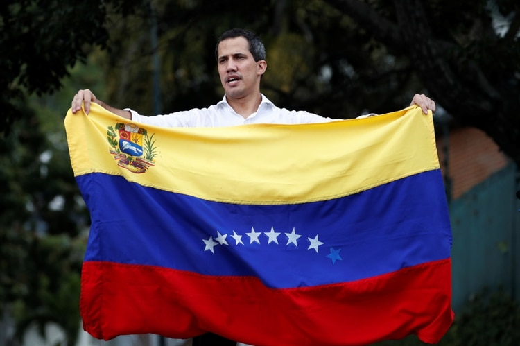 Venezuelan opposition leader Juan Guaido, who many nations have recognised as the country's rightful interim ruler, waves the Venezuelan flag at a gathering with supporters near Bolivia's embassy in Caracas, Venezuela, November 16, 2019. REUTERS/Carlos Garcia Rawlins
