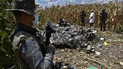 Handout picture released by Guatemala's Army press office showing soldiers standing guard around rubble after a plane carrying drugs crashed in Santa Marta Salinas village, Chisec municipality, Guatemala, on September 23, 2020. - Two people died Wednesday in northern Guatemala when a plane that flew in illegally from Venezuela with a shipment of drugs collapsed, the army announced. (Photo by - / Guatemala's Army / AFP) / RESTRICTED TO EDITORIAL USE - MANDATORY CREDIT AFP PHOTO / GUATEMALAN ARMY - NO MARKETING NO ADVERTISING CAMPAIGNS -DISTRIBUTED AS A SERVICE TO CLIENTS
