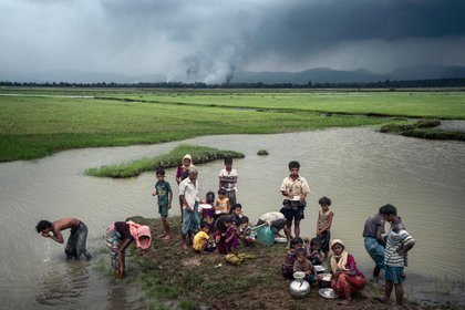 Refugiados rohinyás en septiembre de 2017 después de cruzar a Bangladés. Las aldeas arden en el fondo (Adam Dean para The New York Times)