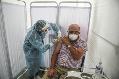 Un trabajador sanitario recibe la vacuna en Lima (ERNESTO BENAVIDES / AFP)