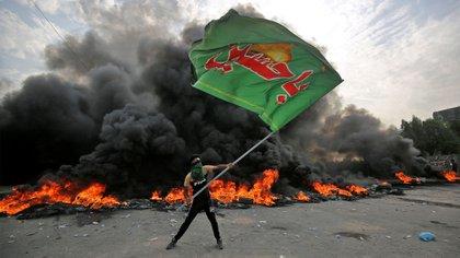 Un manifestante sostiene una bandera con el logo de Hezbollah (AFP)