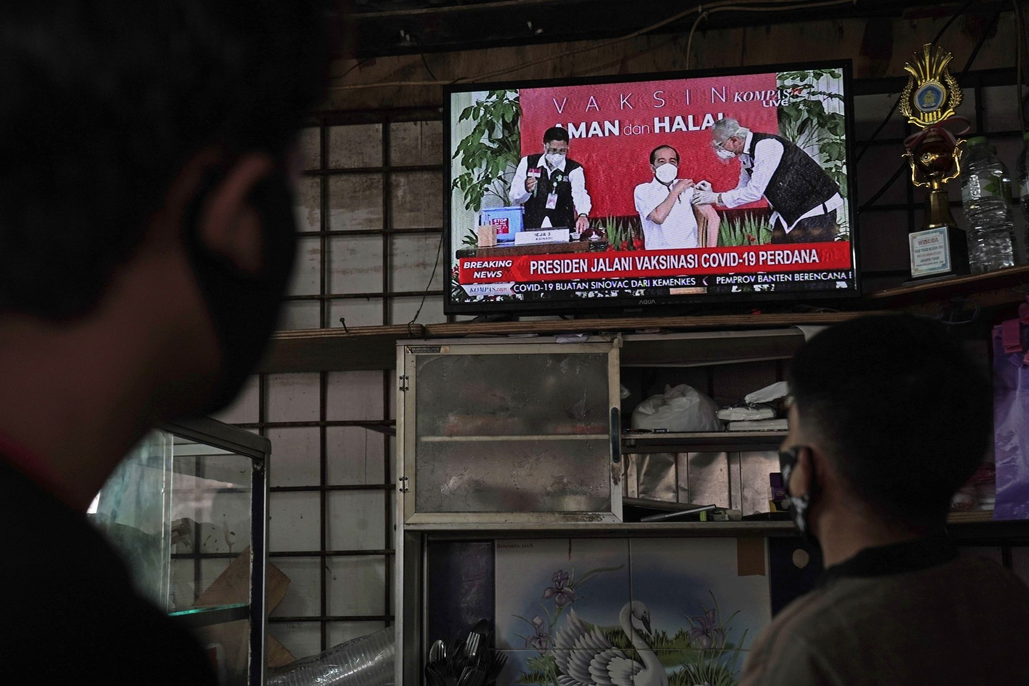 People watch a live news broadcast of Indonesia's President Joko Widodo receiving a dose of the Sinovac Biotech Ltd. Covid-19 vaccine, in Jakarta, Indonesia, on Wednesday, Jan. 13, 2021. Jokowi, as the first president's widely know, received the first dose of China's Sinovac vaccine in a televised event as he seeks to build public confidence in the shots.