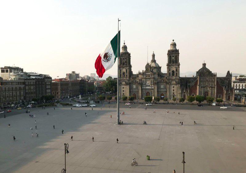 Personas caminan cerca de la bandera nacional y la catedral metropolitana en una plaza del Zócalo parcialmente vacía mientras continúa el brote de la enfermedad por coronavirus (COVID-19), en Ciudad de México, México, 25 de marzo de 2020. REUTERS / Henry Romero /Foto de archivo