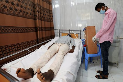 Mohamed Adawe, un ingeniero mecánico de 21 años, está de pie junto a un paciente que utiliza su respirador caseroen su casa en el distrito de Hodan de Mogadiscio, Somalia, el 6 de mayo de 2020 (REUTERS/Feisal Omar)