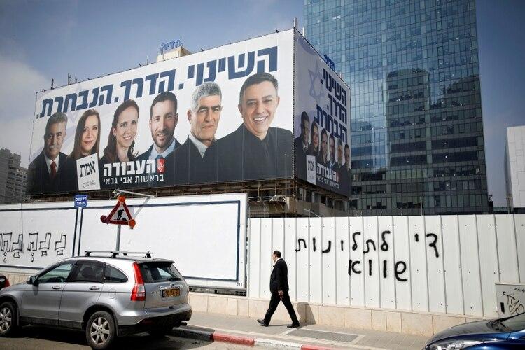 Un hombre camina frente a un propaganda del partido Laborista en Tel Aviv (REUTERS/Amir Cohen)