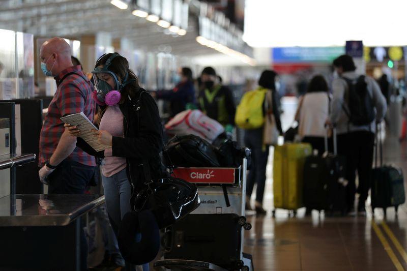 Una mujer se prepara para registrarse en el Aeropuerto Internacional de Santiago (REUTERS/Iván Alvarado/Archivo)