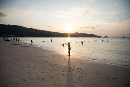 PHUKET, THAILAND - JANUARY 17: A small group of people gather at a relatively empty Patong Beach on January 17, 2021 in Phuket, Thailand. Thailand's tourism-dependent economy was already on life-support before a resurgence of Covid-19 infections, with GDP expected to contract by six per cent in 2020, millions unemployed and record household debt continuing to soar. A fresh lockdown to combat the virus has thrown broad parts of the economy into an extended decline. (Photo by Sirachai Arunrugstichai/Getty Images)