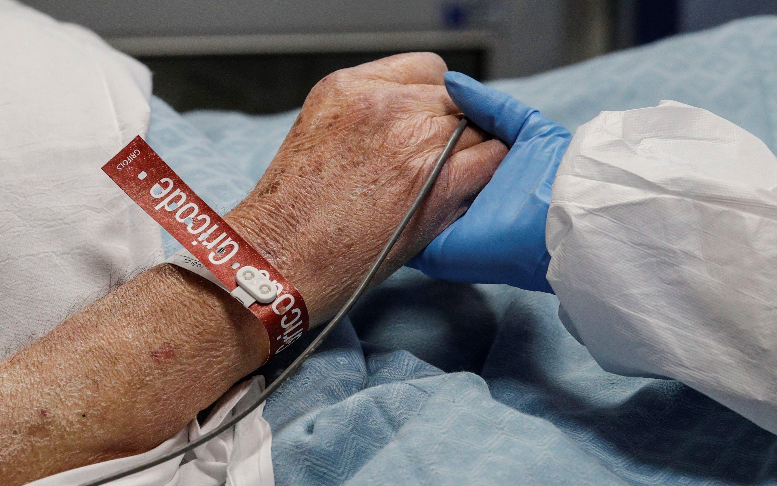 Una enfermera toma de la mano a un paciente de Covid en un hospital de Roma. EFE/EPA/Giuseppe Lami