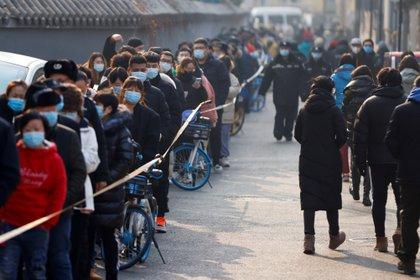 Personas en cola para someterse a un test de coronavirus en Beijing (REUTERS/Carlos Garcia Rawlins)