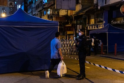 A resident carrying daily necessities returns to an area under lockdown in the Jordan area of Hong Kong, China, on Sunday, Jan. 24, 2021. Hong Kong imposed a temporary lockdown on thousands of residents for the first time to carry out mandatory testing of the coronavirus, with authorities warning the move will be repeated if needed to contain the outbreak.