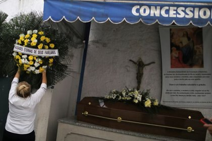 Una trabajadora de cementerio sostiene un ramo de flores junto al ataúd de Maria do Perpetuo Socorro Lavareda, de 77 años, quien murió por COVID-19, antes de su entierro en el cementerio de Sao Joao Batista, en Río de Janeiro, Brasil. 23 de junio 2020. REUTERS/Pilar Olivares