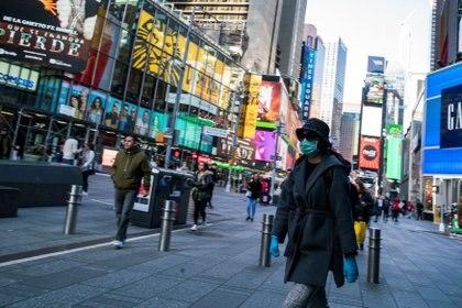 Una mujer pasea con guantes y mascarilla por Times Square. REUTERS/Eduardo Munoz