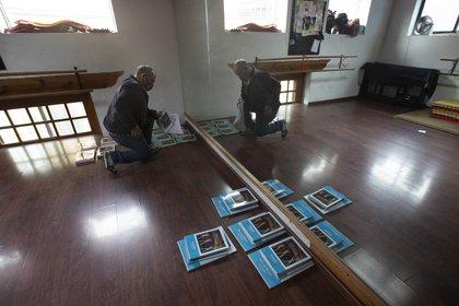 El empleado de la escuela Joel Barbas organiza libros de texto para que los padres los recojan, en una habitación de la escuela Casa del Colibri vacía en medio de la nueva pandemia de coronavirus, mientras los estudiantes regresan a clases pero no a las escuelas en la Ciudad de México, el lunes 24 de agosto de 2020. (Foto AP / Marco Ugarte)
